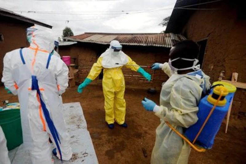 Un trabajador sanitario desinfecta a un compañero antes de acceder a la casa de una mujer de 85 años sospechosa de haber muerto por causa del Ébola