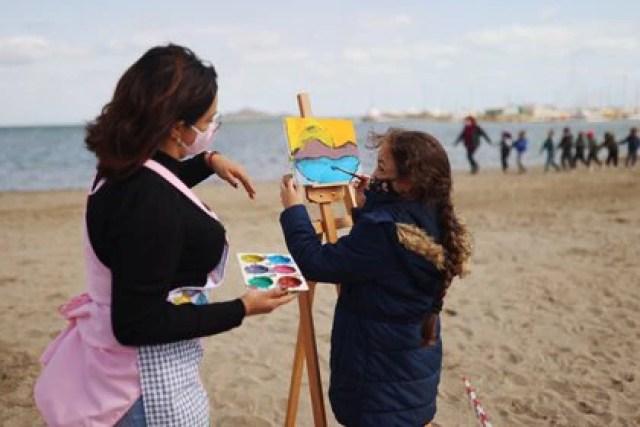 Una maestra junto a una alumna durante una clase de pintura (REUTERS/Nacho Doce)