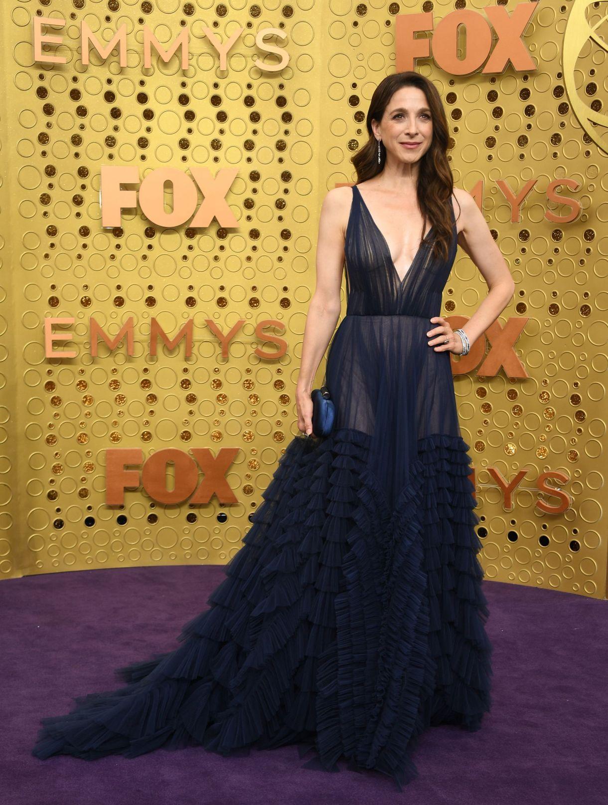 La Marin Hinkle optó para la alfombra violeta de los EMMY 2019 un diseño realizado en seda plisado con gran escote y transparencias que completó con pulseras plateadas, aros gota y clutch de raso