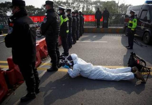 El camarógrafo de Reuters Martin Pollard lleva un traje protector mientras filma en el puente del río Yangtse en Jiujiang, provincia de Jiangxi, China