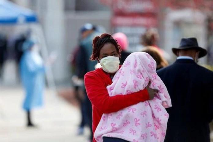 Una mujer sostiene a un bebé mientras camina junto a gente que espera en línea para realizarse exámenes durante el brote global de COVID-19, la enfermedad causada por el nuevo coronavirus, afuera del Roseland Community Hospital en Chicago, Illinois, Estados Unidos. 7 abr, 2020. REUTERS/Joshua Lott