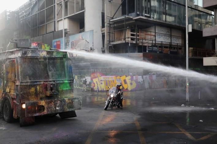 Un motociclista junto a un vehículo de la policía antidisturbios que dispara cañones de agua durante una protesta contra el gobierno, el 29 de noviembre de 2019. (REUTERS/Pablo Sanhueza)