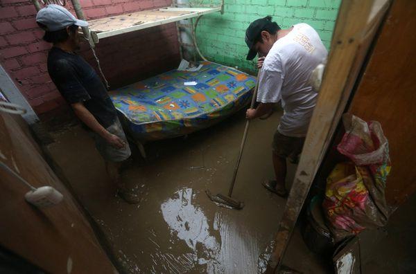 Sobrevivientes de la inundación sacan agua de su hogar. (REUTERS)