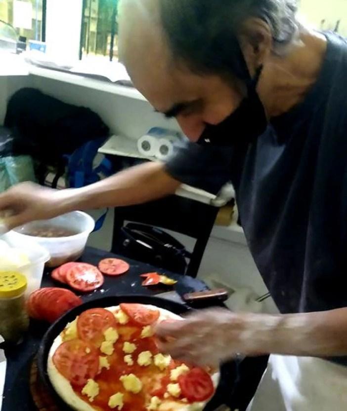 Juan Almirón preparando una pizza, mientras un cliente espera en la puerta