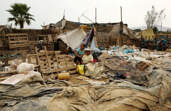 Una familia se sienta en los restos de que lo era su casa que fue destruida por las inundaciones. (REUTER)