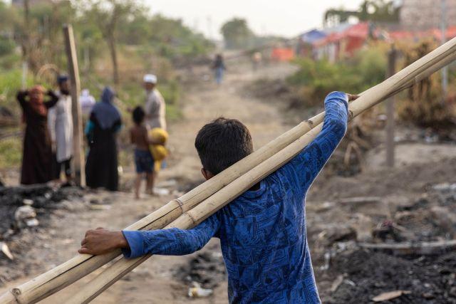 Un refugiado rohingya lleva palos de bambú a un refugio temporal después de que un incendio destruyera un campo de refugiados rohingya el sábado por la noche, en Nueva Delhi, India, 14 de junio de 2021.