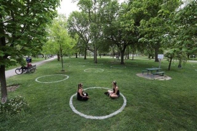 Dos mujeres se sientan en un campo donde se pintaron círculos para ayudar a los visitantes a mantener el distanciamiento social en el parque Trinity Bellwoods en Toronto, Ontario [28 de mayo de 2020] (Reuters/ Chris Helgren)