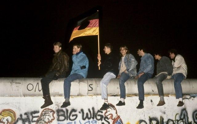 Un joven con la bandera de la Alemania Oriental con su escudo central recortado, sobre el muro, la noche del 9 de noviembre.