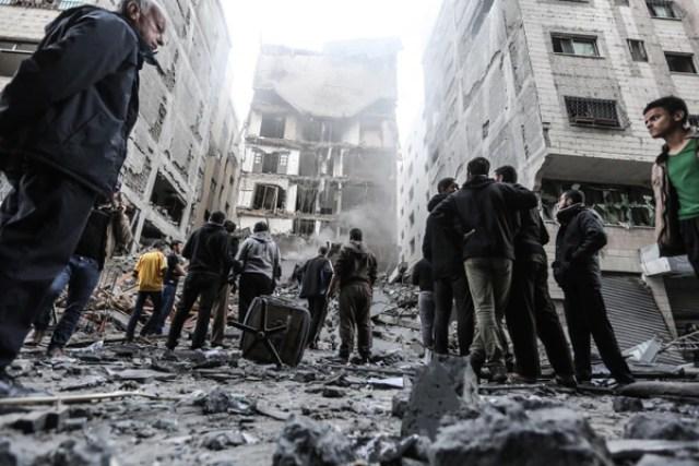 Palestinos frente a un edificio golpeado por bombardeos israelíes en Gaza (MAHMUD HAMS / AFP)