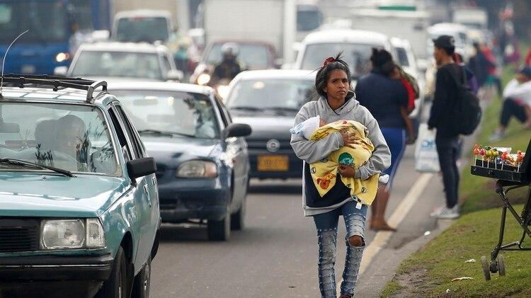 Una inmigrante venezolana con un bebé camina por el costado de una avenida en Bogotá, Colombia (AP Photo/Fernando Vergara)