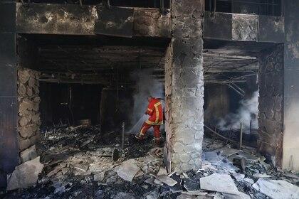 Un bombero rocía agua dentro de una sucursal de banco abandonada que fue incendiada durante las protestas nocturnas en Beirut, Líbano, el 12 de junio de 2020 (REUTERS/Mohamed Azakir)