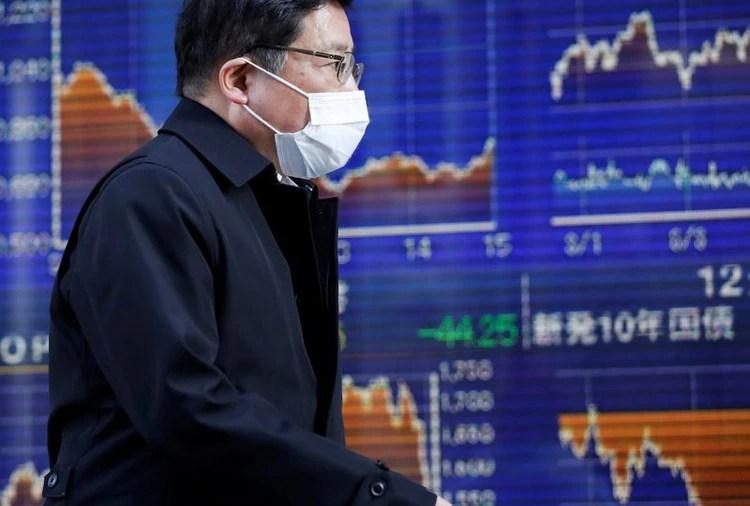 Un hombre con una máscara protectora para el coronavirus caminando delante de una pantalla que mueestra los movimientos del índice Nikkei en Tokio.