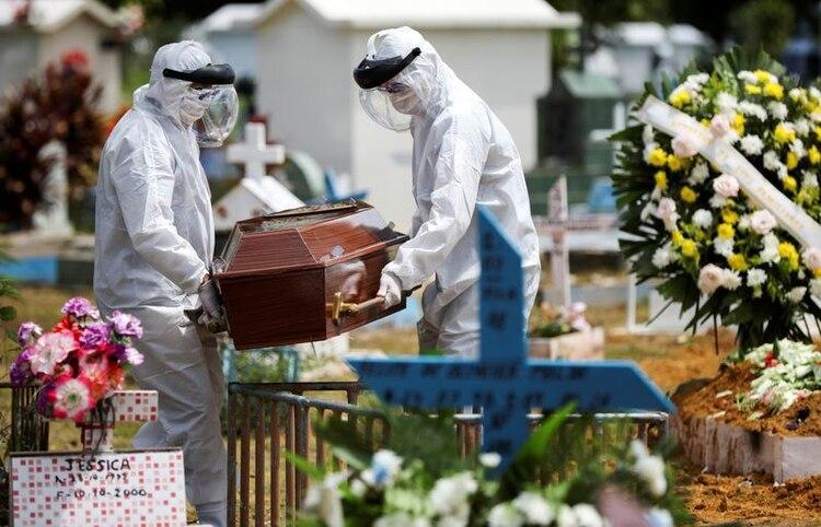 Sepultureros usando trajes protectores llevan el ataud de una mujer de 68 años Natalina Cardoso Bandeira, quien murió debido a la enfermedad del coronavirus (COVID-19), en el cementerio del Parque Taruma en Manaus, Brasil, 10 de abril del 2020. REUTERS/Bruno Kelly