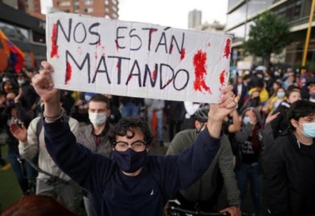 """Un manifestante sostiene un cartel en el que se lee """"Nos están matando"""" durante una protesta en Bogotá, Colombia, el 4 de mayo de 2021. REUTERS/Nathalia Angarita"""