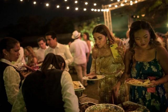 Huéspedes de la boda se sirven comida en la Hacienda Camburito de Acarigua