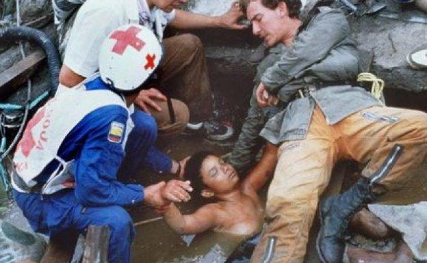 Socorristas tratan de rescatar sin éxito el cuerpo de Omayra Sánchez que quedó atrapado entre los escombros de su casa después de que una avalancha causada por la erupción del Nevado del Ruiz destruyera el pueblo de Armero en Colombia