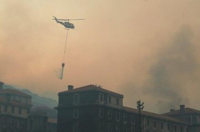 Un helicóptero lanza agua sobre la biblioteca. (REUTERS/Mike Hutchings)