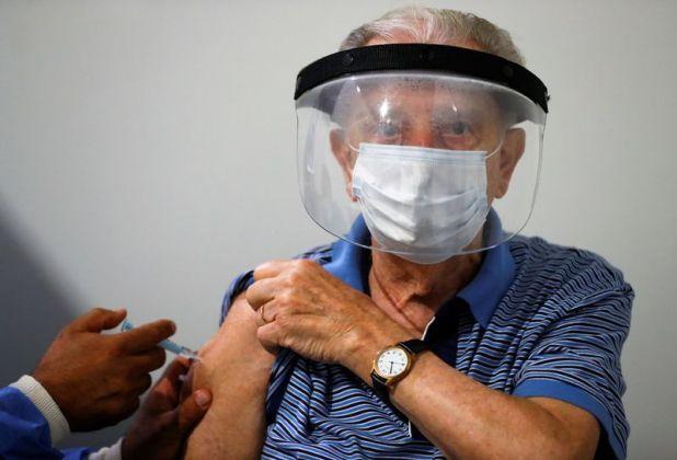 Un trabajador de la salud aplica una dosis de la vacuna de Oxford-AstraZeneca contra el coronavirus producida por el Instituto Serum de India (SII), a un hombre mayor en un centro de vacunación en Buenos Aires, Argentina, el 22 de febrero de 2021. REUTERS/Agustin Marcarian