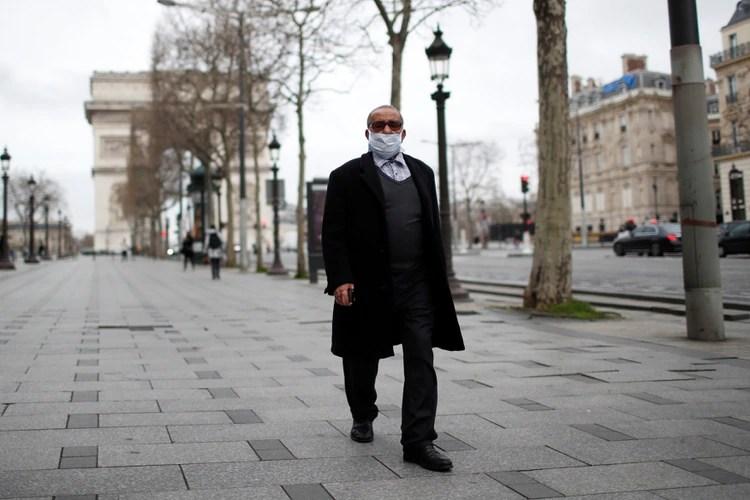 Un hombre camina por Champs Elysees, cerca del Arco de Triunfo, en una Paría casi desierta.
