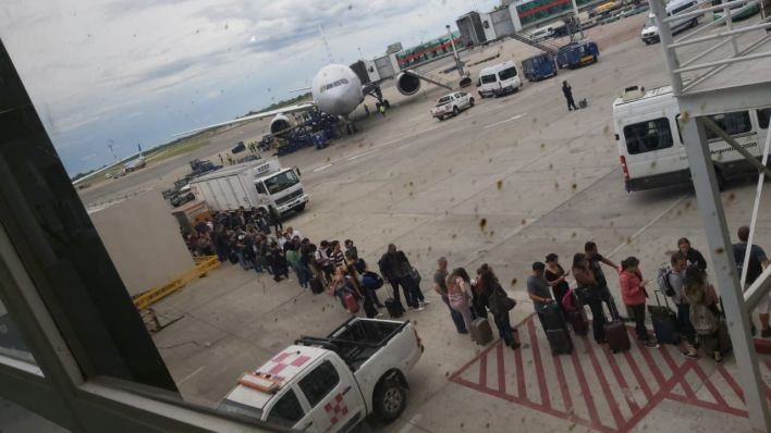 La imagen tomada durante la mañana del sábado, cuando decenas de pasajeros tuvieron que formar fila en la pista de aterrizaje, debido al colapso en el sector de Migraciones