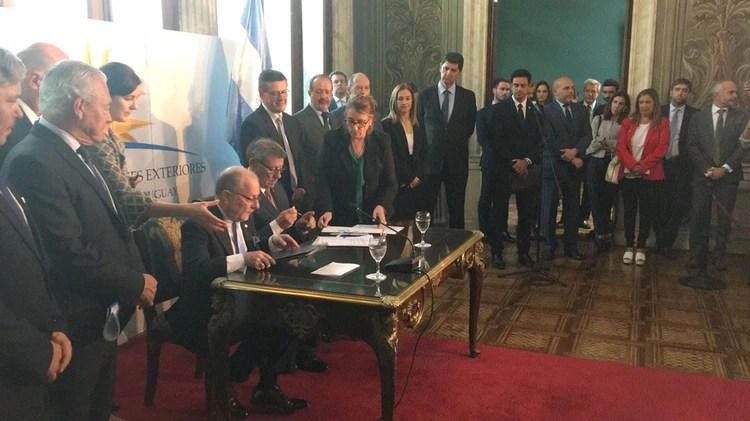 La firma del convenio entre el canciller Jorge Faurie y su par, Rodolfo Nin Novoa. (@MRREE_Uruguay)