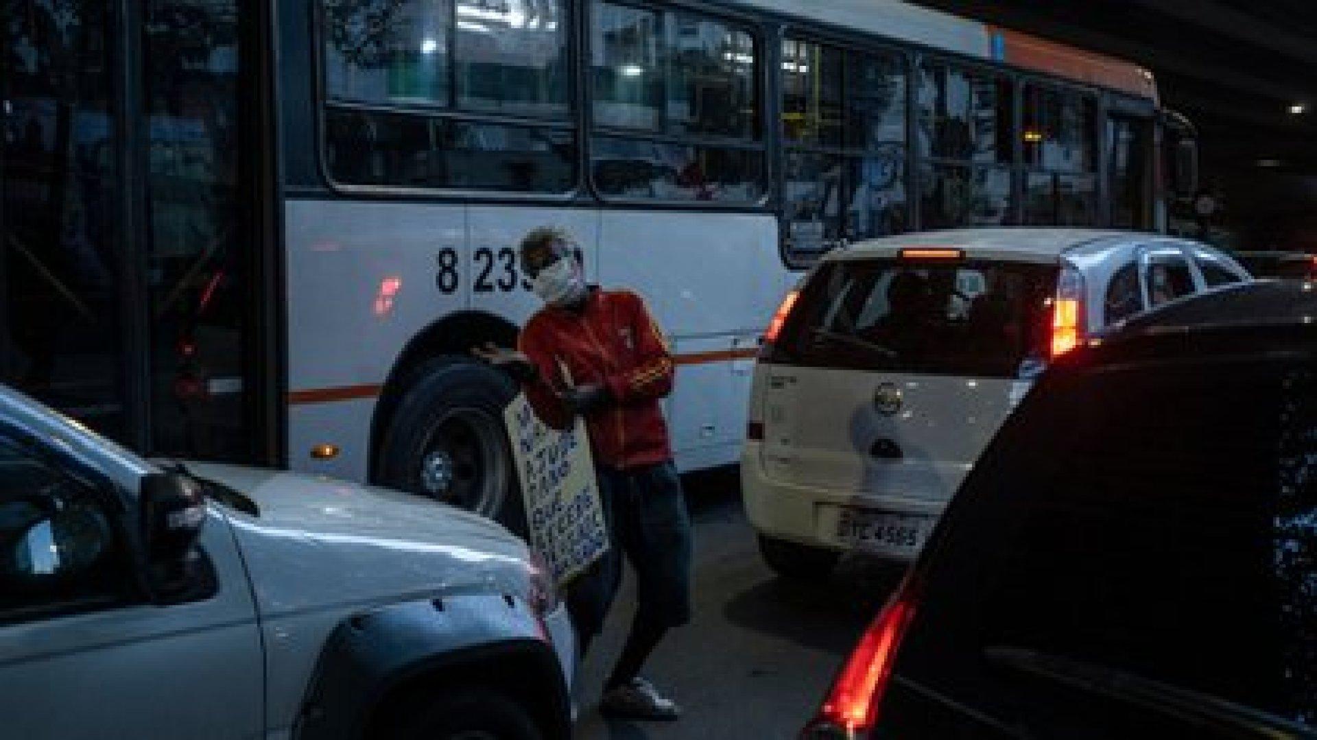 Ismael dos Santos pide unas monedas en un semáforo. (Victor Moriyama / The New York Times)