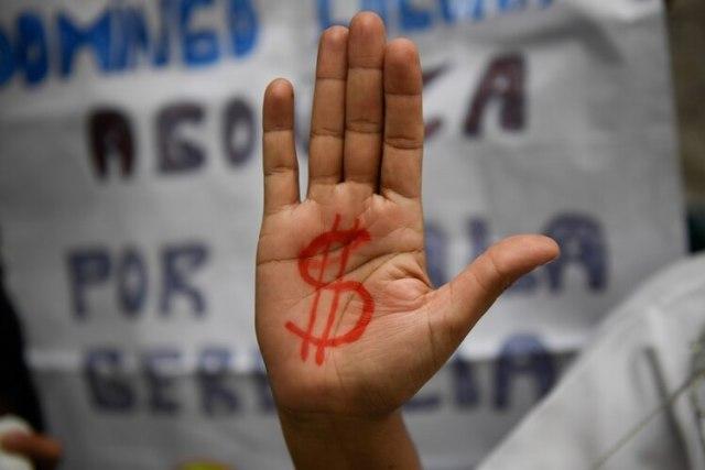 Una enfermera protesta por las pobres condiciones de los hospitales en Venezuela (AFP)