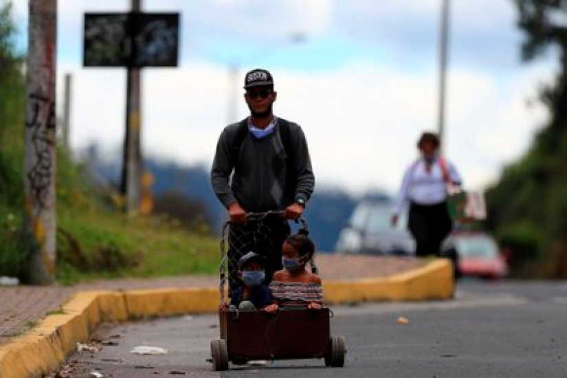 A Venezuelan citizen and two children walk on the road, back in Venezuela (EFE / José Jácome)