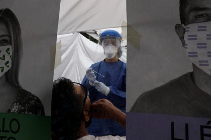 A health worker in personal protective equipment (PPE) conducts a test for the coronavirus disease (COVID-19) to a patient, in the municipality of Tlahuac, one of the highly contagious zones of the city, as the coronavirus disease (COVID-19) outbreak continues in Mexico City, Mexico July 15, 2020. REUTERS/Carlos Jasso