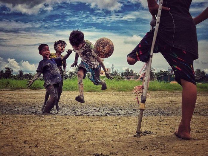 """El tercer clasificado en esta categoría fue Zarni Myo Win (Myanmar) con la foto """"I want to play"""" (Quiero jugar) que tomó con un iPhone 7 Plus enYangon, Myanmar. """"Un niño que perdió una pierna miraba a sus amigos jugar fútbol y dijo que quería jugar al fútbol"""", dijo Zarni sobre esta imagen."""