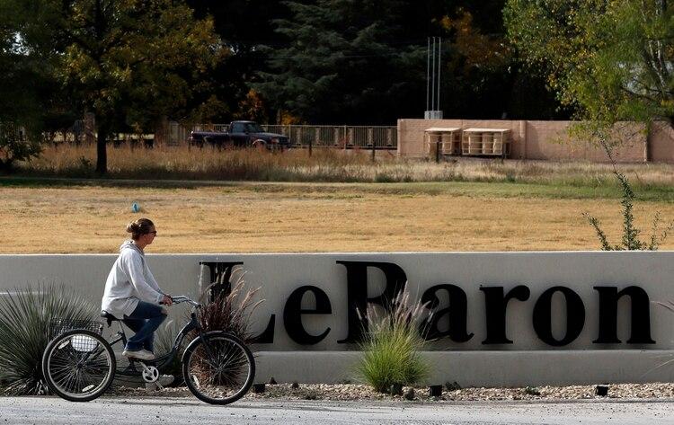 Una mujer pasa en bicicleta por delante del cartel de Colonia LeBarón, una comunidad establecida por miembros de la familia extendida LeBarón en el estado de Chihuahua, en el norte de México, el 6 de noviembre de 2019. (AP Foto/Marco Ugarte)