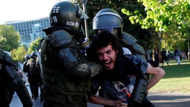 Dos agentes retienen a un joven (Reuters)