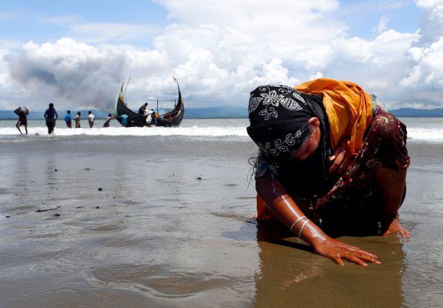 Una mujer refugiada rohingya exhausta toca la orilla después de cruzar la frontera entre Bangladesh y Myanmar en barco a través del Golfo de Bengala, en Shah Porir Dwip, Bangladesh 11 de septiembre de 2017.