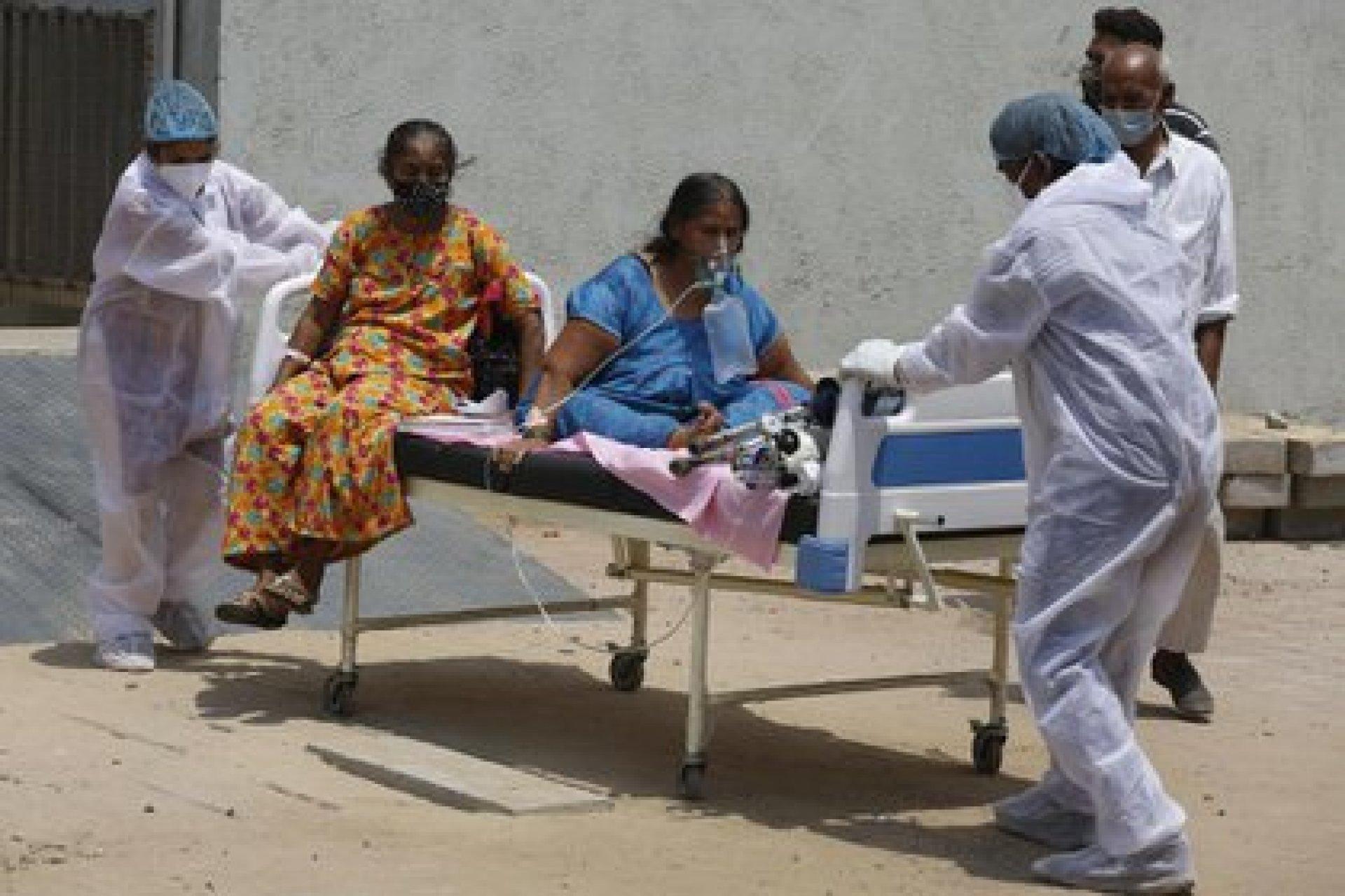 Un trabajador de la salud transporta a los pacientes para trasladarlos de un hospital dedicado al COVID-19 a otro hospital para desocupar la cama para nuevos pacientes, en el hospital Civil de Ahmedabad, India, el martes 13 de abril de 2021 (AP Photo / Ajit Solanki).