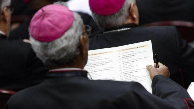 Un obispo lee el programa de la segunda jornada (GIUSEPPE LAMI / POOL / AFP)