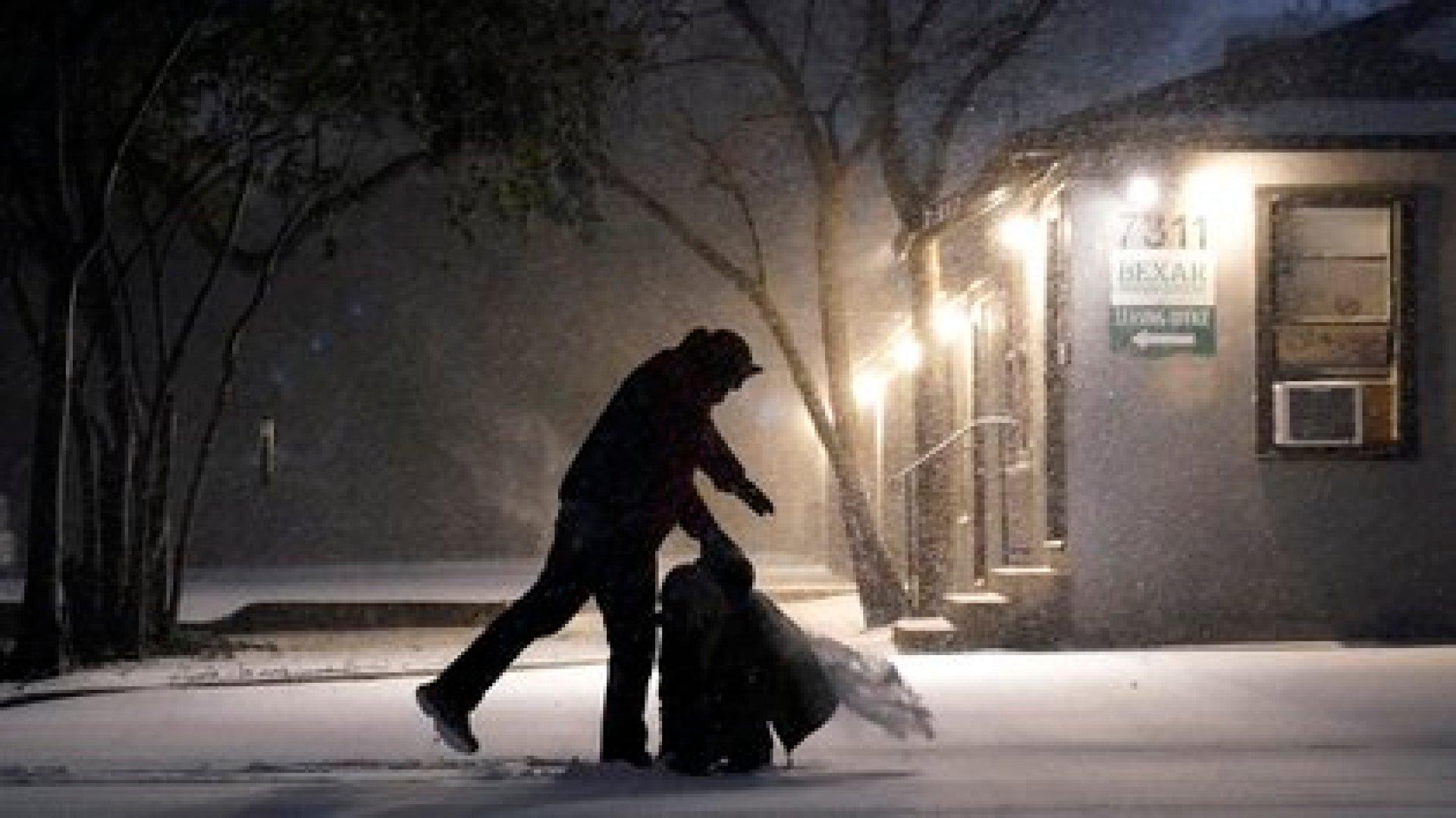 Un hombre caminando en la noche nevada de San Antonio, Texas (AP Photo/Eric Gay)