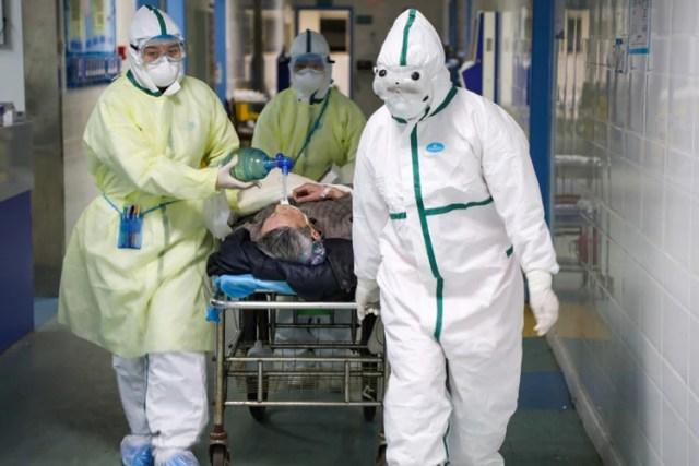 Trabajadores en trajes protectores trasladan a un paciente en una sala aislada de un hospital del distrito de Caidian, provincia de Hubei (China Daily via REUTERS)
