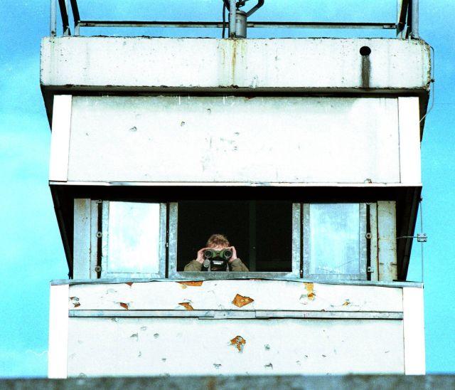 Una oficial de Alemania Oriental observa por binoculares desde una torre de control del muro