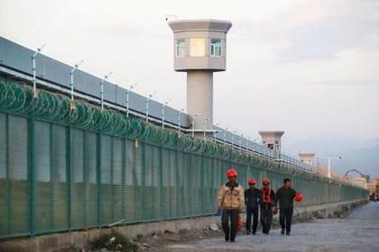 Trabajadores caminan junto a la valla perimetral de lo que se conoce oficialmente como centro de formación profesional en Dabancheng, en la Región Autónoma Uigur de Xinjiang, China, el 4 de septiembre de 2018 (REUTERS/Thomas Peter)