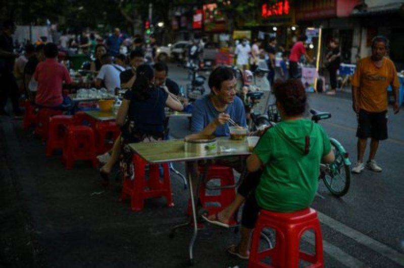 Esta foto tomada el 4 de agosto de 2020 muestra a personas comiendo durante la tarde frente a un pequeño restaurante en Wuhan, en la provincia central de Hubei en China, donde nació el coronavirus (AFP)