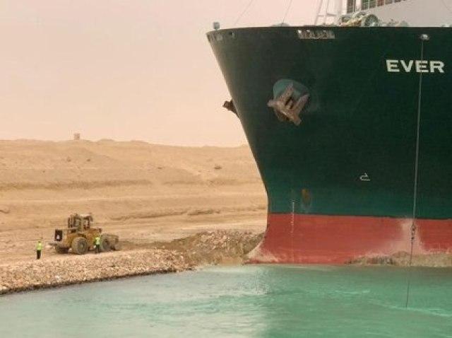Trabajadores junto a un buque portacontenedores que fue golpeado por un fuerte viento y encalló en el Canal de Suez, Egipto