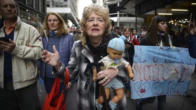 Una manifestante con un bebé de juguete