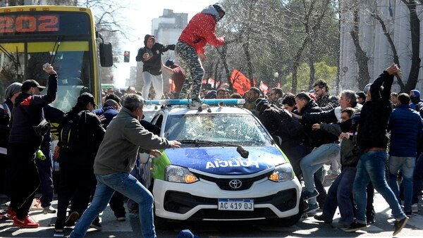 Los manifestantes rompen uno de los patrulleros de la policía bonaerense (NA)