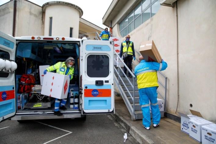 Voluntarios de la asociación Misericordia que llevan máscaras faciales recogen paquetes donados por una confitería del sur de Italia en Catania, Italia, el 15 de abril de 2020. (Antonio Parrinello/REUTERS)