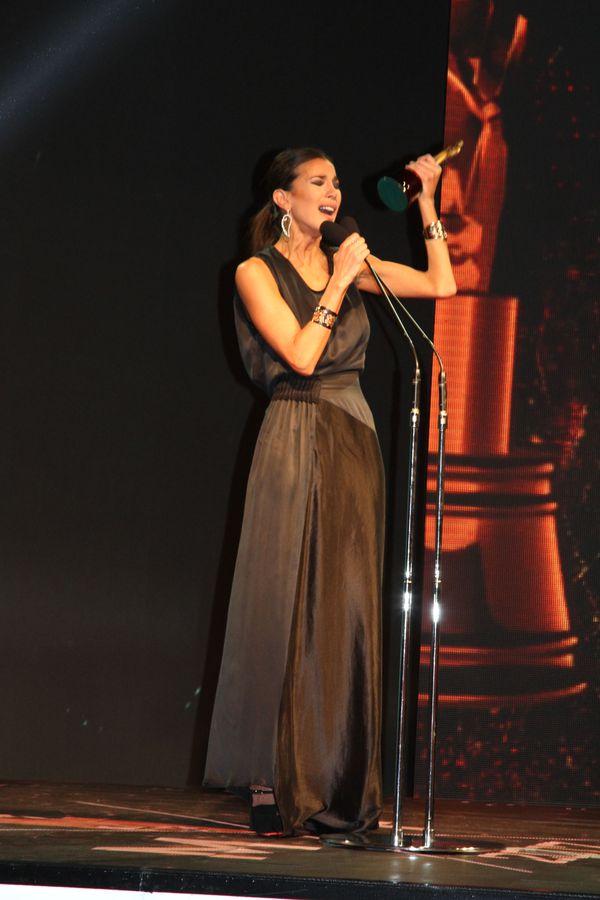 Andrea Rincón sorprendio con un look total black en seda con drapeado en la cintura, bijoux con esclavas en plateado y aros en forma de hoja