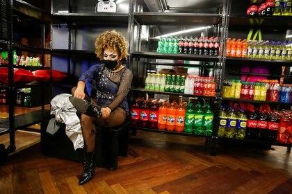 La drag queen Belaluh McQueen se pone sus botines en discoteca LGBTQ+ Valetodo Downtown, que reabrió sus puertas como una tienda de alimentos mientras dure la restricción de cierre para clubes nocturnos debido a la pandemia del coronavirus (COVID-19), en Lima, Perú. 26 de junio de 2020. REUTERS/Sebastián Castañeda
