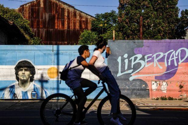 Dos personas andan en bicicleta más allá de una pintura callejera con la imagen de la leyenda del fútbol Diego Armando Maradona en Buenos Aires (REUTERS/Ricardo Moraes)