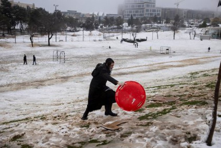 An ultra-Orthodox Jewish boy plays with the snow in a park on a snowy morning in Jerusalem, February 18, 2021. REUTERS / Ronen Zvulun