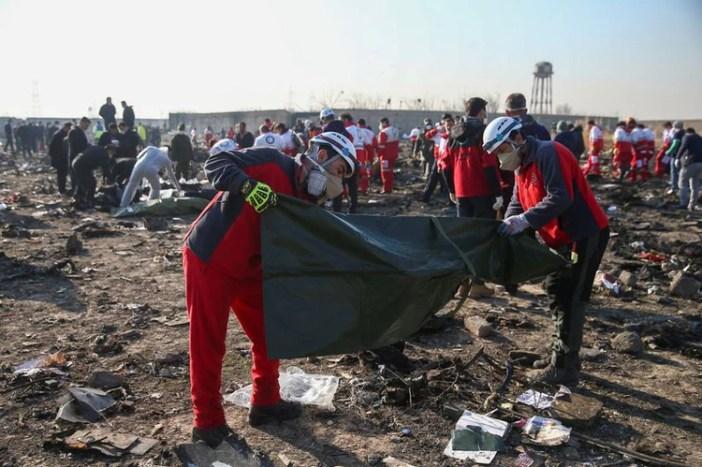 Trabajadores de la Media Luna Roja revisan bolsas de plástico en el sitio donde el avión de Ukraine International Airlines se estrelló después del despegue del aeropuerto iraní Imán Jomeini, en las afueras de Teherán. 8 de enero de 2020. Nazanin Tabatabaee/WANA (West Asia News Agency) vía REUTERS.