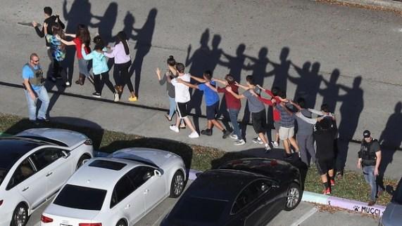 Estudiantes del colegio en Florida, víctima del último ataque, salen del edificio custodiados por la policía. (AFP)